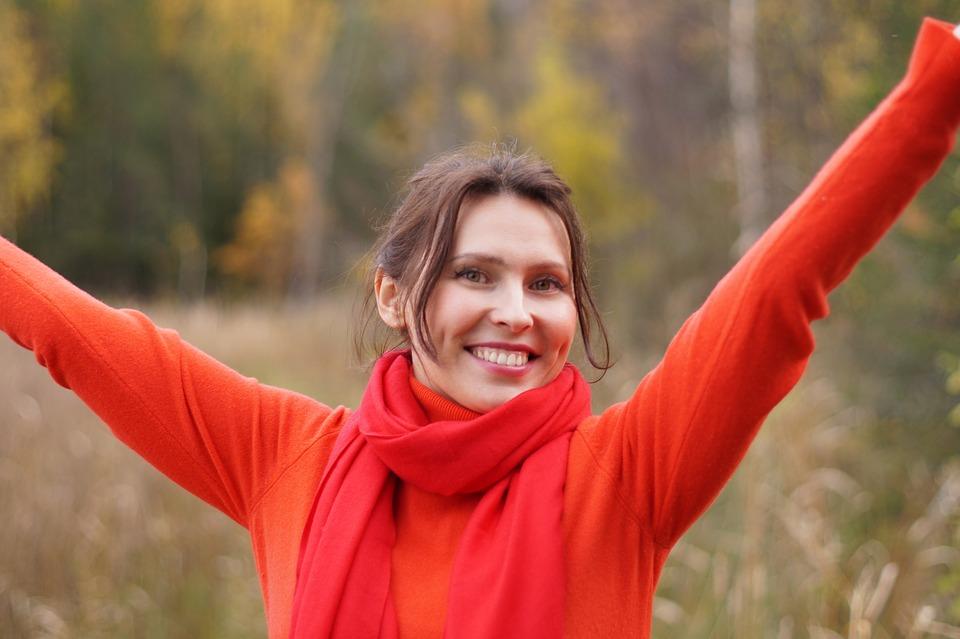 mulher sorrindo de braços abertos